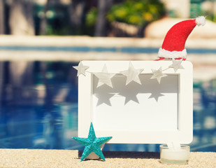 Christmas photo frame against swimming pool