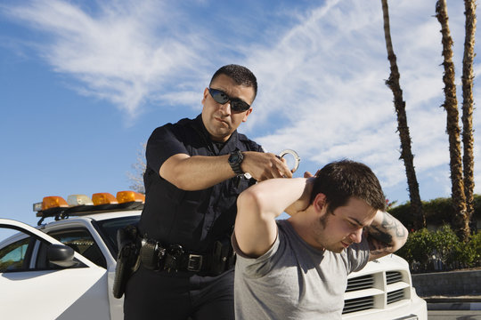 Police officer arresting young man by patrol car