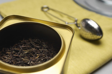 Closeup of tea leaves in a container with strainer on napkin