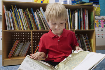 Happy schoolboy reading picture book in classroom