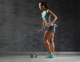 Sporty young woman with dumbbells on gray background