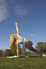 Young Caucasian woman performing yoga exercises on mat at park