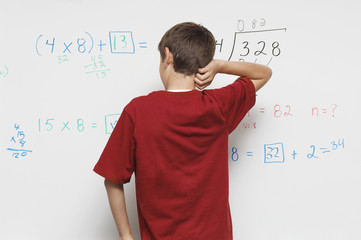 Rear view of a teenage boy scratching head against white board in classroom