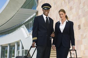 Portrait of happy pilot and flight attendant outside building
