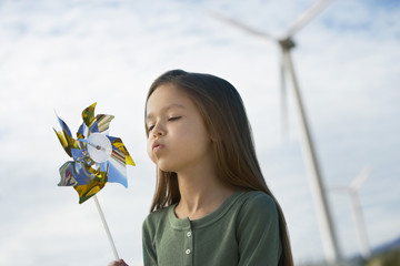 Cute little Caucasian girl blowing toy windmill at wind farm