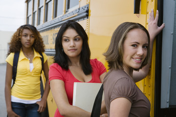 Portrait of a beautiful high school student with classmates getting on school bus