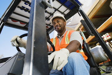 Low angle view of a happy male industrial worker driving forklift at workplace