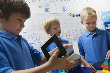 Three little schoolboys assembling toy pieces in a classroom