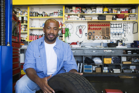 Portrait of a happy African American male mechanic working on a tire