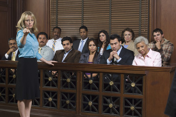 Portrait of a female prosecutor standing by jury box in court