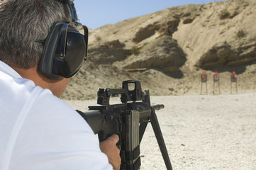 Rear view of a man with protectors aiming machine gun at firing range