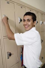 Portrait of smiling high school boy opening locker