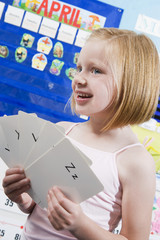 Elementary student with alphabet flash cards in classroom