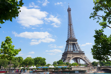 Eiffel Tower over Seine river with tree green leaves, Paris, France