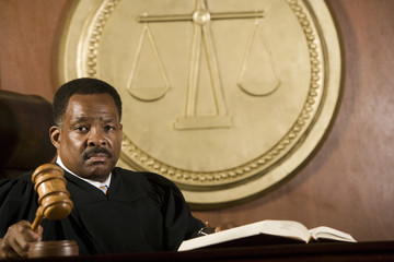 Portrait of a male judge holding wooden gavel in courtroom