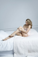 Full length of sensuous young woman wearing stockings in bed