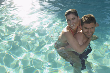Portrait of a happy young man giving woman piggy back in swimming pool