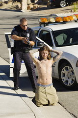 Young shirtless man kneeling with police officer aiming gun by car
