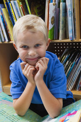 Portrait of a cute schoolboy with picture book in school library