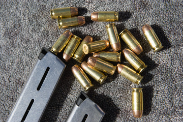 Closeup of gun magazines and bullets on grey carpet
