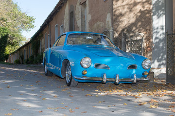 very old sport car, an old timer blue in the street