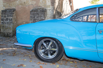 the rear side with wheels od an old timer car blue ocean