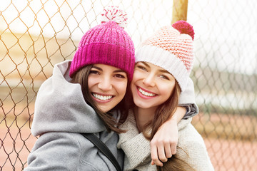 Two female best friends in knit beanies and coats hugging and smiling