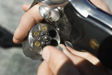 Closeup of a man's hand loading bullets into a gun