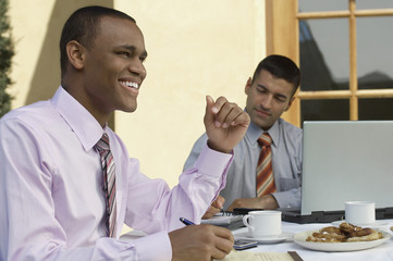Two multiethnic businessmen working at an outdoor cafe table