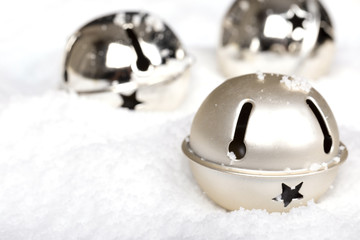 Silver jingle bells in the snow. Christmas themed image.