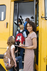 Portrait of female teacher writing on paper while students boarding school bus