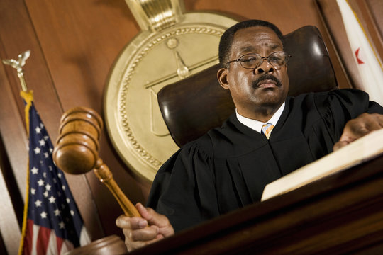 An African American male judge forming sentence in the courtroom