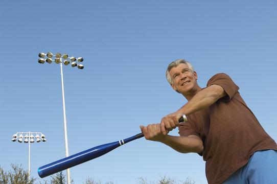 Active Caucasian man swinging baseball bat against blue sky