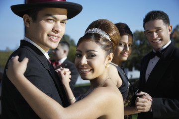 Happy couple dancing together with friends in the background at Quinceanera