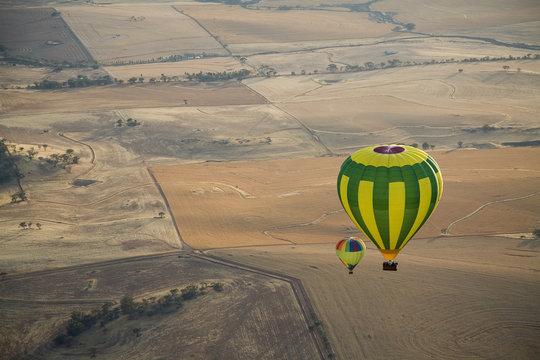 Aerial view of two hot air balloons floating over brown countryside near Northam in Western Australia
