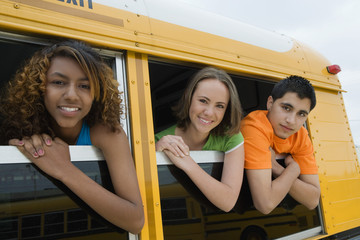Portrait of teenagers looking out from windows of a yellow school bus