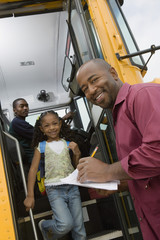 Male teacher helping elementary students get off the school bus