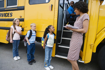 Female teacher taking a note of students before boarding school bus