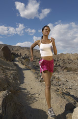 Full length of a young woman jogging in mountains