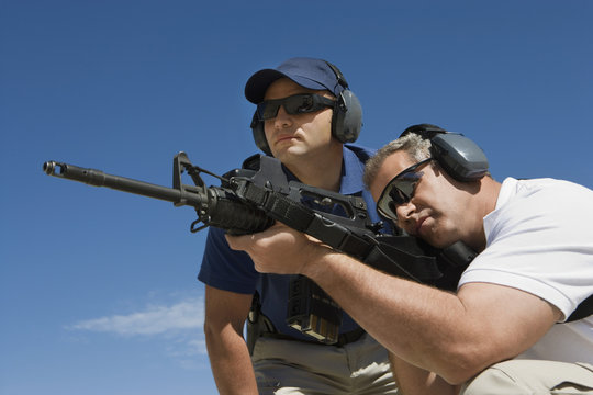 Low angle view of instructor with man aiming machine gun at firing range