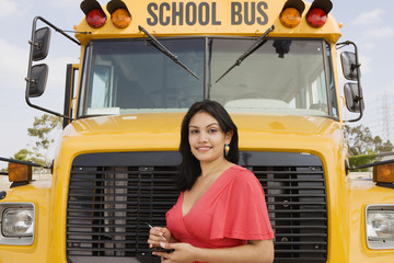Portrait of a pretty teenage girl using PDA while standing in front of school bus