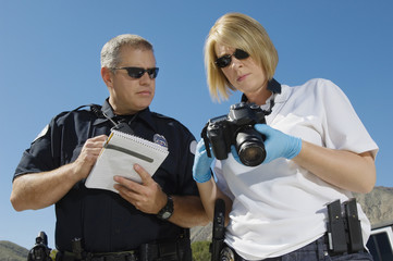 Low angle view of police officers looking at the recorded picture in camera