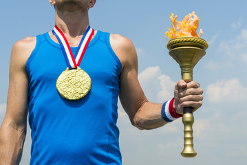 American gold medal athlete standing with sport torch in front of blue sky