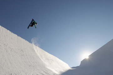 Low angle view of snowboarder performing stunts in park against blue sky on a sunny day