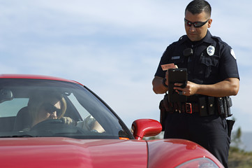 Traffic cop writing a ticket for woman sitting in sports car