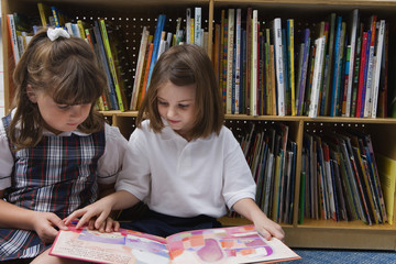 Cute schoolgirls looking at a picture book in library