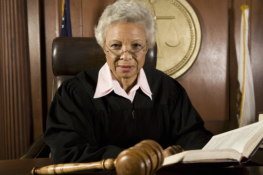 Portrait of a senior female judge with book in courtroom