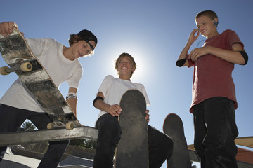 Low angle view of teenage boys with skateboards smiling against blue sky