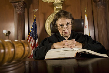 Portrait of female judge with law book in the courtroom