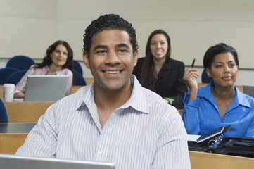 Happy businessman in presentation with female business colleagues sitting in the background